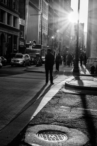 Silhouette of man crossing street creates long shadow from late-day sun - Philadelphia Street Photography