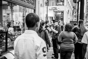 Man enjoys a fine beverage on conversation on a busy sidewalk. - Philadelphia Street Photography