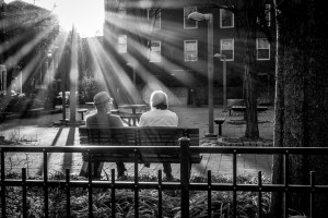 Late day sun (with small apeture starburst) illuminating a couple sitting on a park bench.