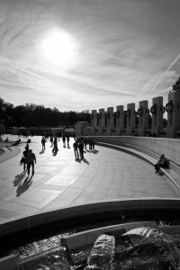 Human silhouettes casting shadows on the grounds of the World War II Memorial in Washington D.C.